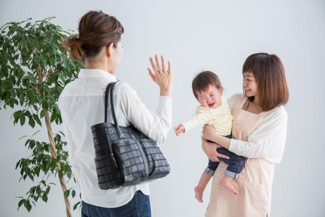 夜間保育に預ける母親から子どもを預かる女性保育士