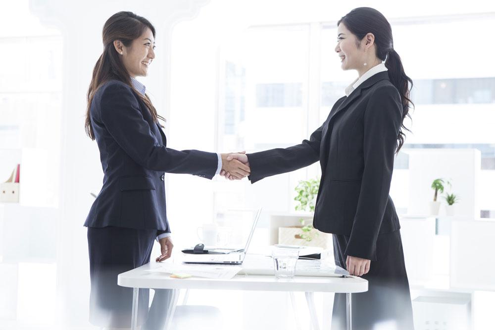 転職でいい職場と巡り会えて、握手を交わす女性たち