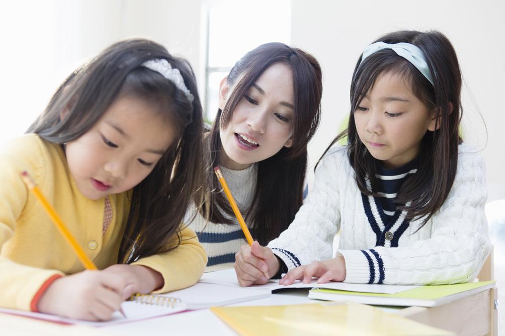 子どもが宿題している様子を見守っている放課後児童支援員