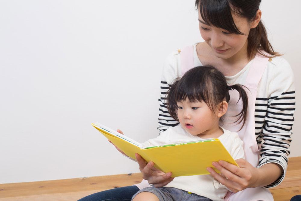 子どもをヒザに乗せて本を読む女性保育士