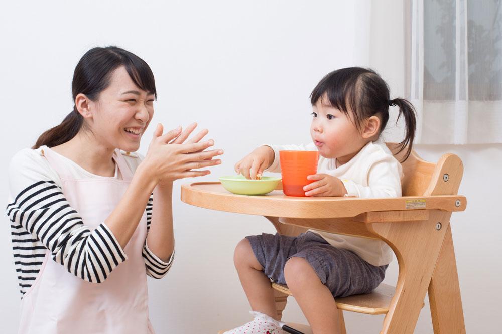 一生懸命ご飯を食べている子どもを笑顔で褒める保育士