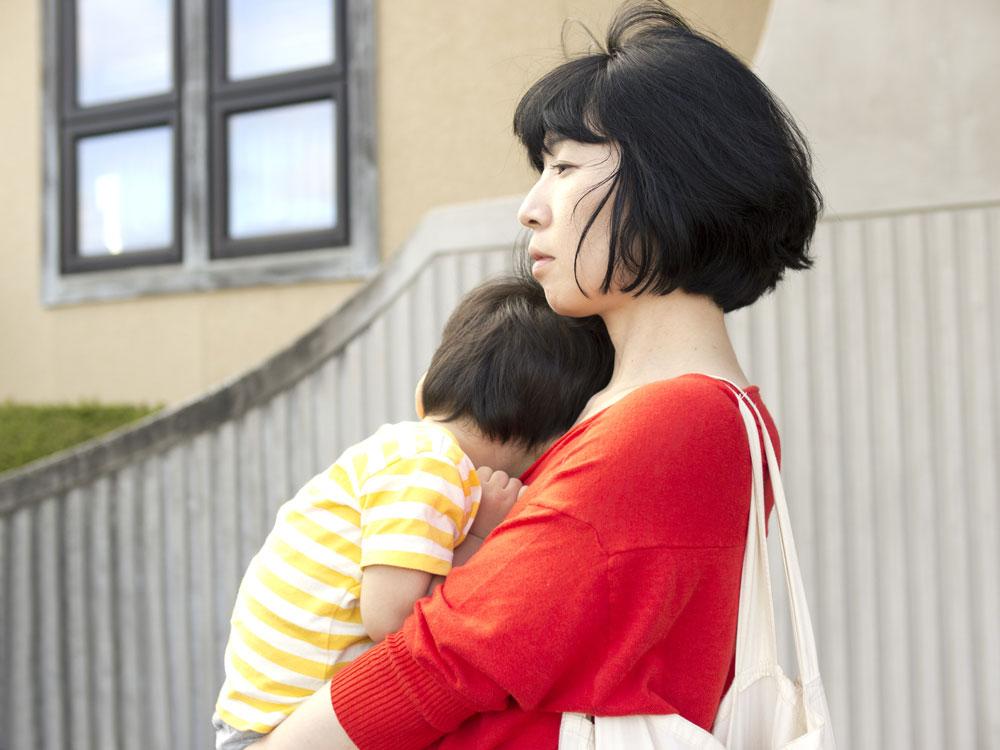仕事帰りに寝ている子どもをだっこして、遠い目をしている女性