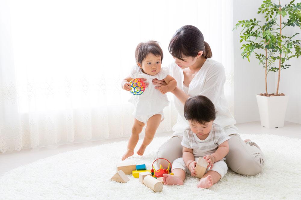 院内保育所で、オモチャで遊ぶ子どもたちを見守る女性保育士