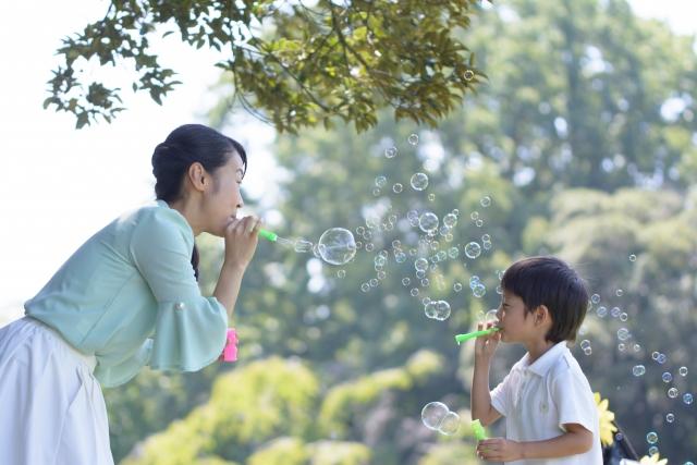 子どもと向かい合ってシャボン玉で遊ぶ女性