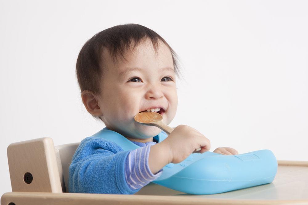 笑顔でスプーンを持ってご飯を食べている赤ちゃん