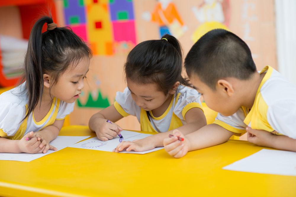 インクルーシブ保育を実施する保育園で一緒にお絵かきをしている3人の子どもたち