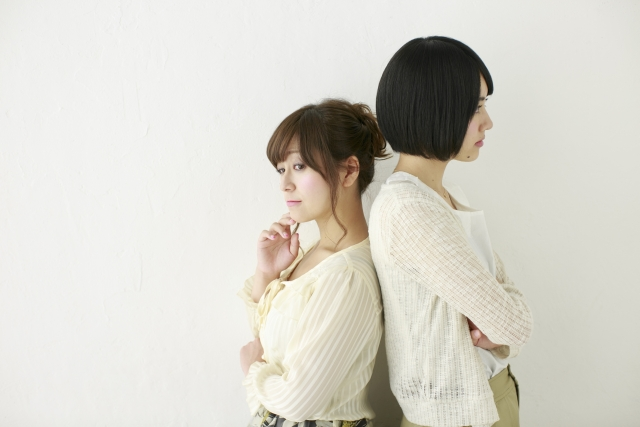 背中を合わせで心の距離を感じる2人の女性