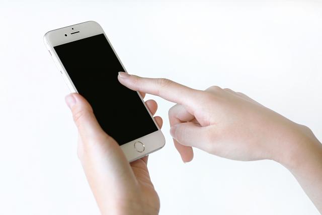 園見学を申し込むためにスマートフォンを触っている女性
